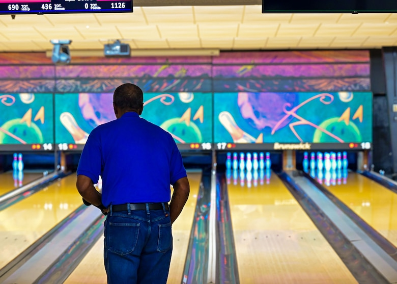 A man looks down a bowling lane as he prepares to throw a ball at the pins at the end of the lane.