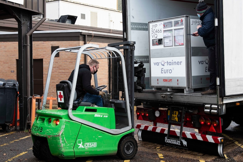 A man in a forklift approaches a container.