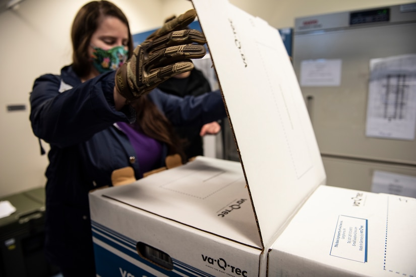 A woman opens a box of vaccines.