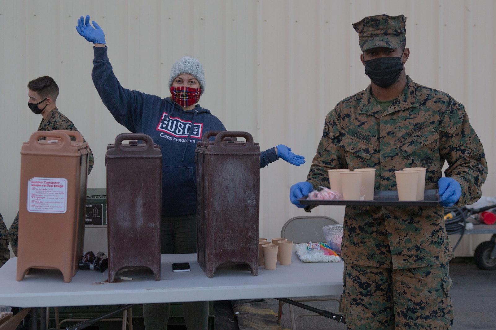 Marines and civilian volunteers from 1st Maintenance Battalion provide hot chocolate to families during the battalion's Winter Wonderland.