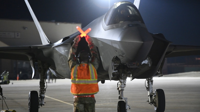 An Air Force maintainer stops an F-35A Lightning II on a flight line.