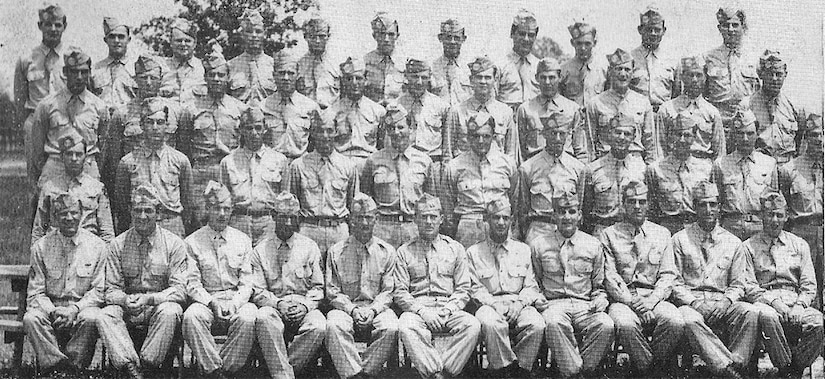 Four rows of soldiers line up for a photo, one behind the other.