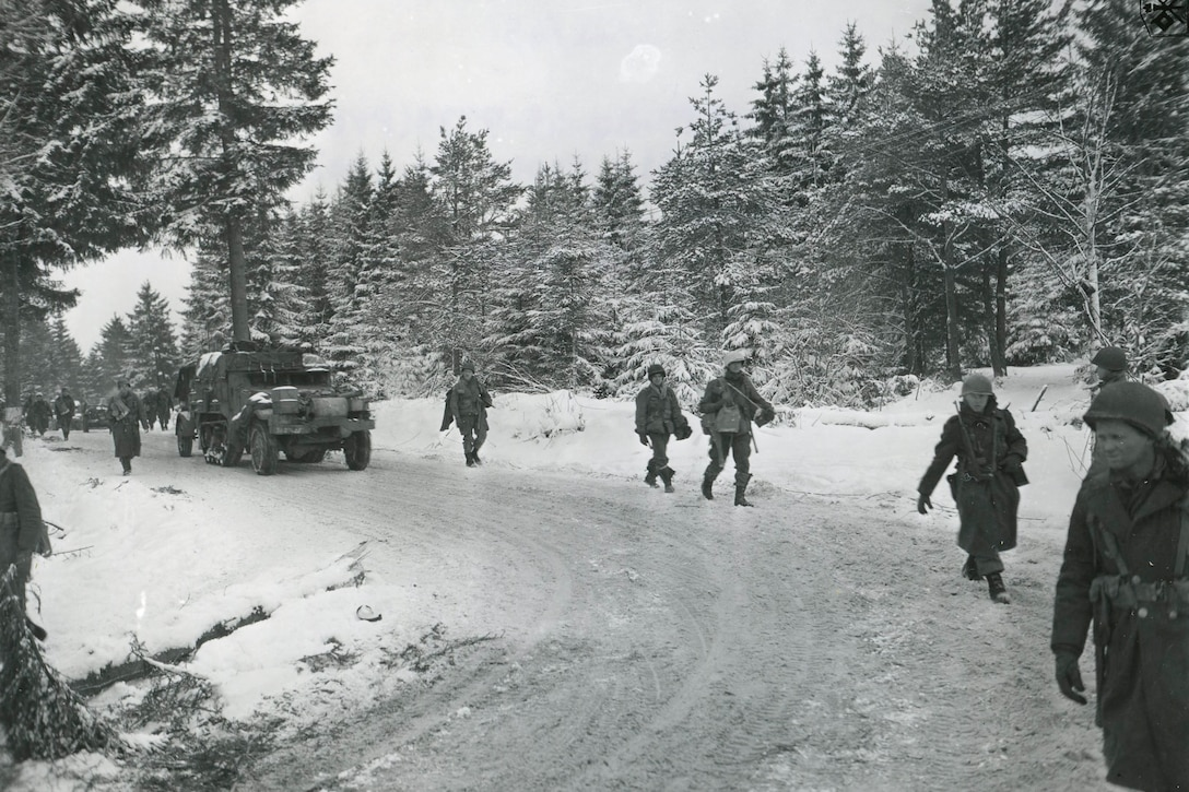 Soldiers march near a vehicle along a winding road in a snow-covered forest.