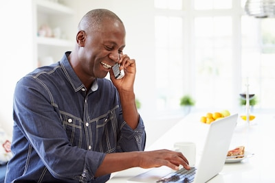man using laptop and cell phone at home