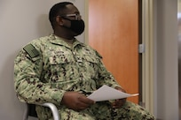Navy Petty Officer 2nd Class John London sits outside a waiting room before receiving one the first COVID-19 vaccines at Brian D. Allgood Army Community Hospital.