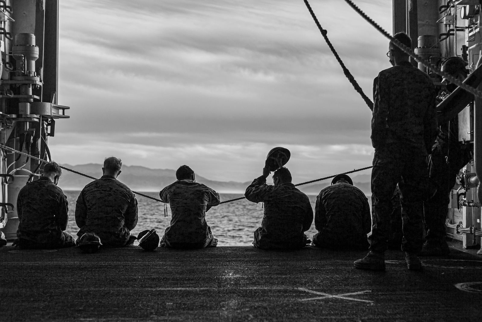 U.S. Marines with Combat Logistics Battalion 1 wait on the side of the USS Portland.