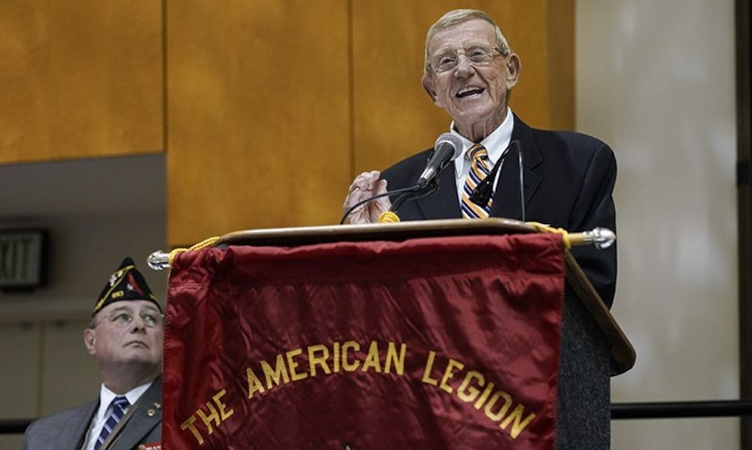 """A man stands at a lectern and speaks into a microphone; the lectern is draped with a banner that reads """"The American Legion."""""""