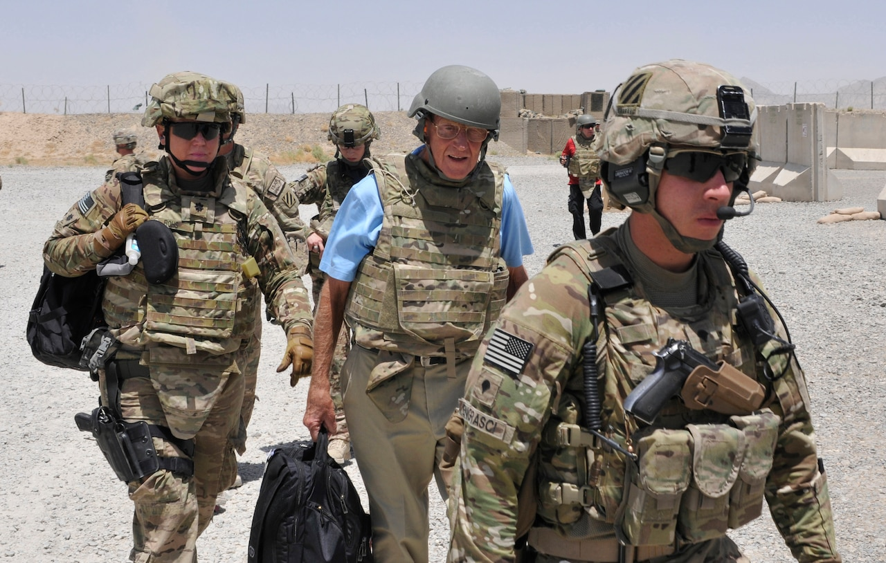 Three men dressed in combat gear walk together as service members stand behind them.