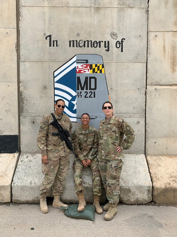 (From left) Tech. Sgt. Lindsey Bryant, Airman 1st Class Bria Bailey, and Senior Airman Jayme Bradley, Airmen assigned to the 175th Maintenance Squadron, Maryland National Guard, pose for a photo in front of a memorial April 16, 2019, during her deployment to Kandahar, Afghanistan.