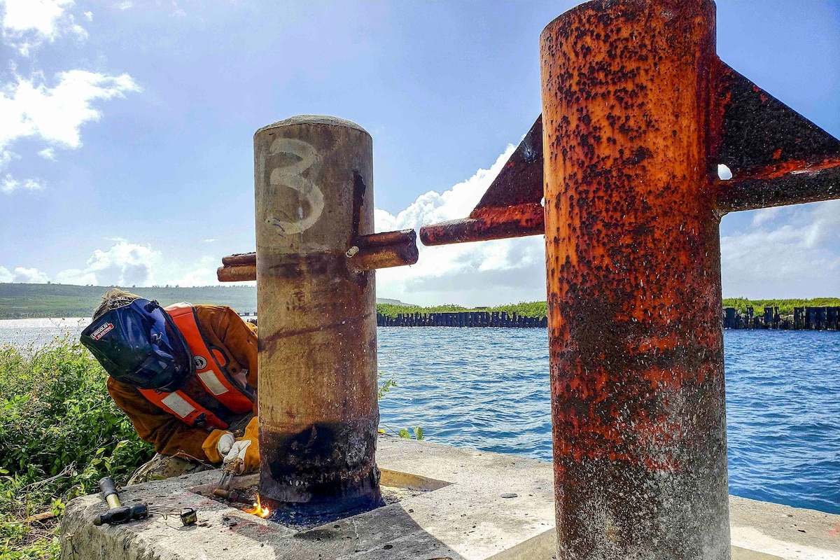 A sailor wearing a protective helmet uses a torch on a deteriorated mooring post.