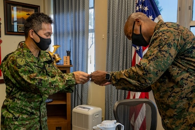 U.S. Marine Corps Col. Henry Dolberry Jr., Marine Corps Air Station (MCAS) Futenma commanding officer, and Japan Ground Self Defense Force (JGSDF) Col. Nobuyuki Ishii, 22nd Rapid Deployment Regiment commander, exchange business cards during a tour at Marine Corps Air Station Futenma, Okinawa, Japan, Nov. 4, 2020. The tour was an opportunity for the JGSDF to conduct a site survey to familiarize themselves with MCAS Futenma's capabilities. (U.S. Marine Corps photo by Lance Cpl. Zachary Larsen)