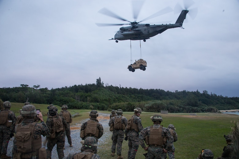 U.S. Marines with Combat Logistics Battalion 31, 31st Marine Expeditionary Unit (MEU) observe a Marine CH-53E Super Stallion aircraft assigned to Marine Medium Tiltrotor Squadron 262 (Reinforced), 31st MEU, carrying a Joint Light Tactical Vehicle Heavy Guns Carrier during a Helicopter Support Team (HST) training exercise as part of MEU Exercise at Kin Blue, Okinawa, Japan on Dec. 17, 2020. HST training is conducted to increase proficiency in logistics tasks and enhance the ability to execute potential contingency missions carried out by the 31st MEU. The 31st MEU, the Marine Corps only continuously forward-deployed MEU, provides a flexible and lethal force ready to perform a wide range of military operations as the premiere crisis response force in the Indo-Pacific region. (U.S. Marine Corps photo by Lance Cpl. Colton Nicks)