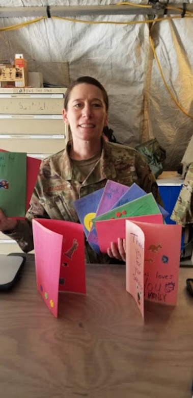 Senior Airman Jayme Bradley, an electrical and environmental specialist for the 175th Maintenance Squadron, Maryland National Guard, poses with cards sent to her from her home church April 8, 2019 during her deployment to Kandahar, Afghanistan.