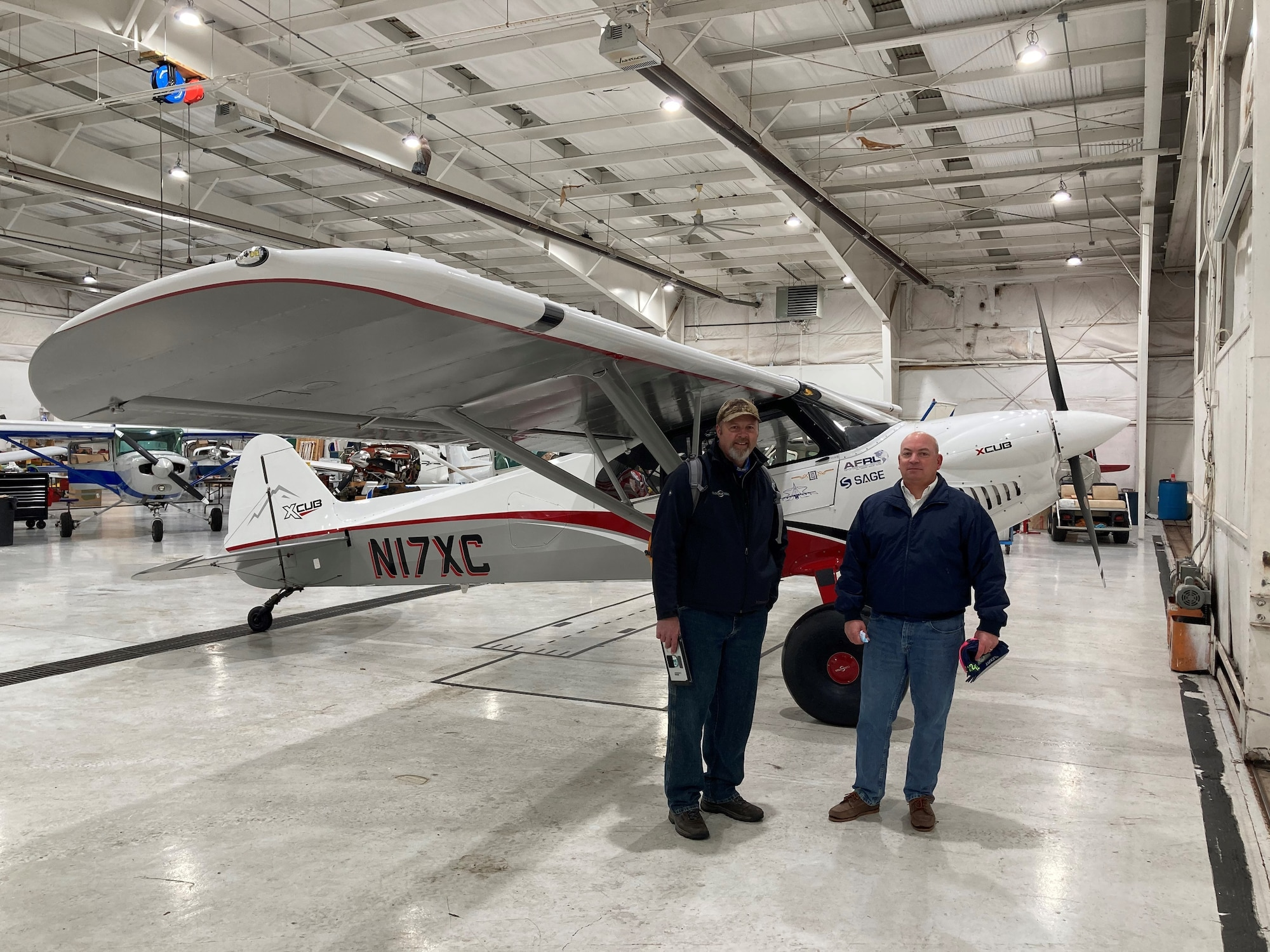 """CubCrafters pilot Mark Keneston (left) and Air Force Research Laboratory pilot Dr. Eric Geiselman are pictured next to AFRL LASH Lysander XCub at the Lewis A. Jackson Regional Airport in Greene County, Ohio, on Dec. 21, 2020. The aircraft made a brief stop before traveling on to the AFRL 711th Human Performance Wing's contracted research flight test organization facility in Maryland, where it will be used to advance the initial """"Lysander"""" personnel recovery flight experiments. (U.S. Air Force photo/Dr. Darrel G. Hopper)"""