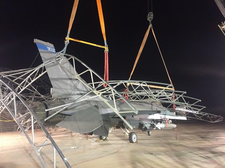 Civil Engineers and aircraft maintenance personnel untangle and remove sunshades after they collapsed on F-16 Fighting Falcons during a storm that caused 91-mile per hour winds at the 407th Air Expeditionary Group in 2018.