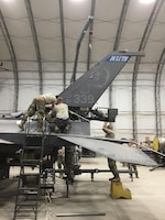 Aircraft maintenance personnel perform maintenance on battle damaged F-16s after a storm that caused 91-mile per hour winds to collapse sunshades at the 407th Air Expeditionary Group in 2018.