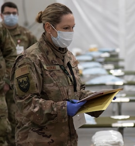 Air Force Maj. Amber Macrae practices going over patient information at the Alternate Healthcare Facility in Essex, Vermont, April 7, 2020. The Vermont National Guard is working with the state of Vermont and emergency response partners in a whole-of-government effort to flatten the curve of the COVID-19 pandemic. Macrae is a medical provider with the 158th Medical Group.