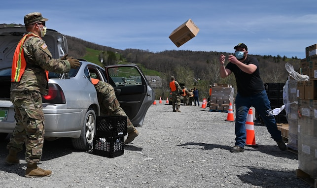 "Vermont National Guard Soldiers and state partners hustle to load meals into vehicles in Peru, Vermont, May 19, 2020. The Vermont National Guard assists the Vermont Food Bank ""Farmers to Families"" program and Vermont Emergency Management provide fresh produce, dairy and prepared meals."