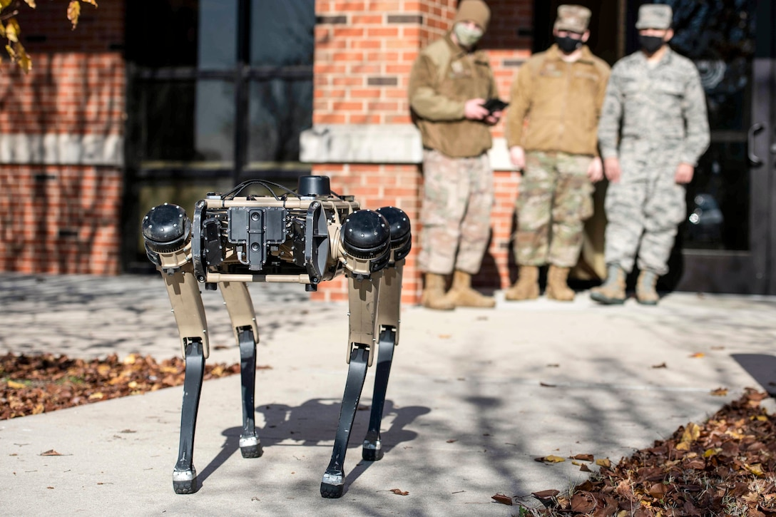 An airman standing outside a building with two others holds a remote control in the background while a robot walks on a path in front of them.