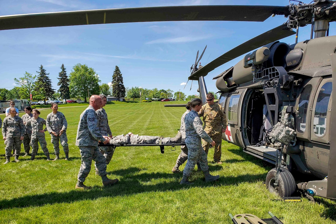 Airmen put a person on a stretcher into a waiting helicopter in a field.