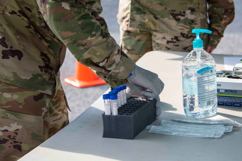 A person with gloved hands puts a vial into a secure container on a table.