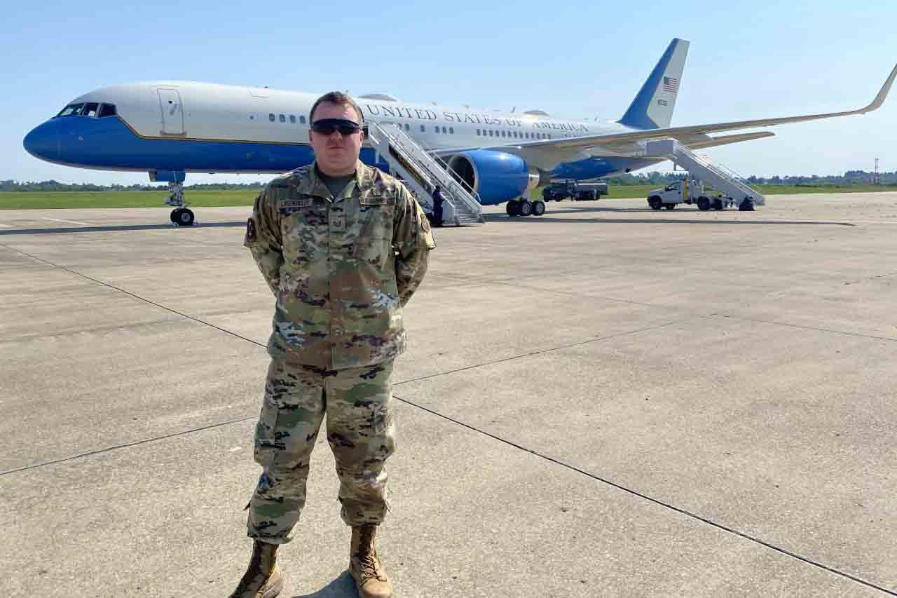 An airman stands on the tarmac in front of a passenger jet.