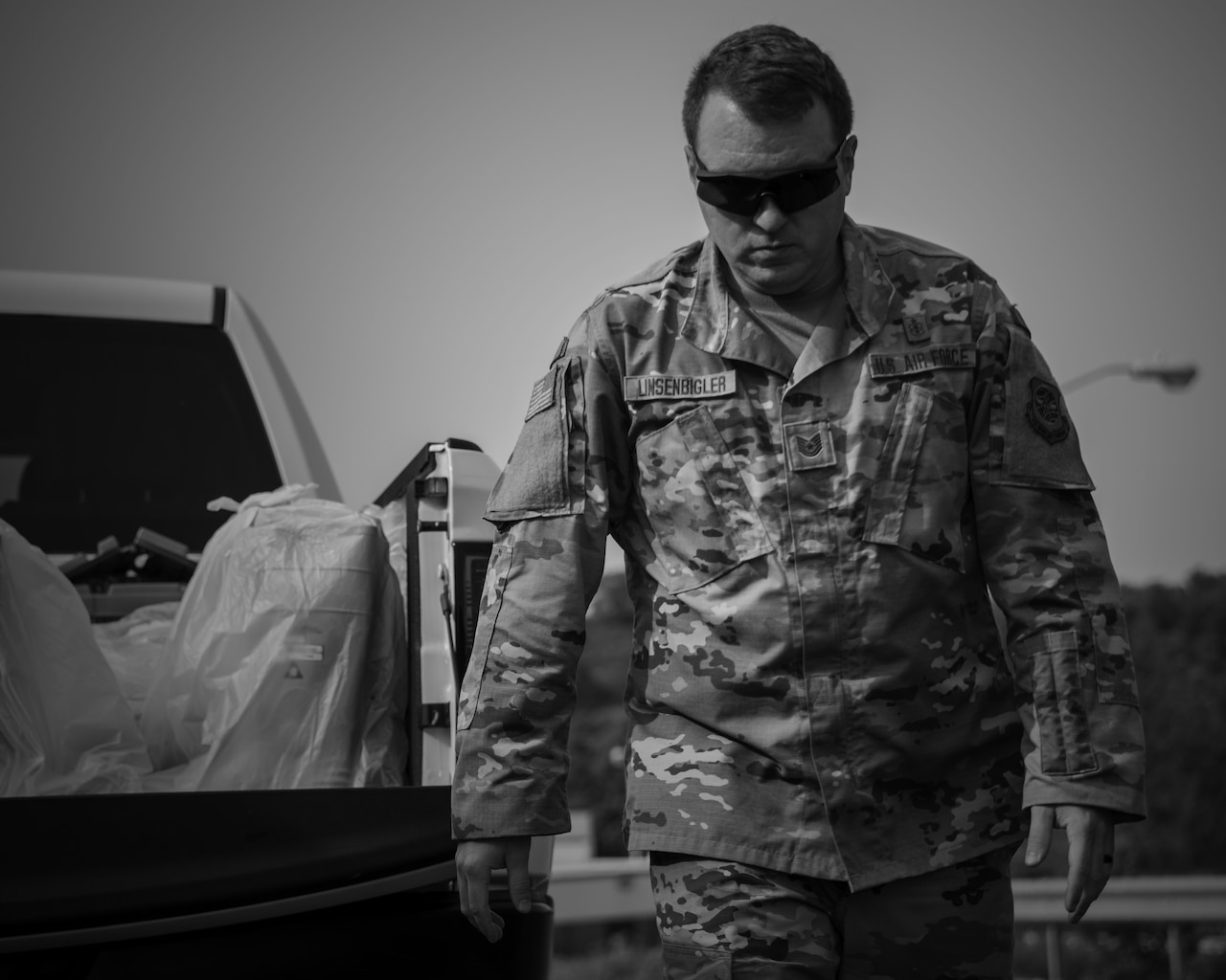 An airman in sunglasses walks away from a pickup truck loaded with supplies.