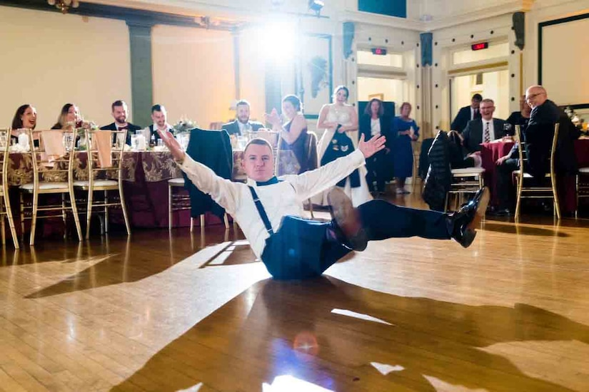 A man sits with his arms and legs up in the air on a dance floor.