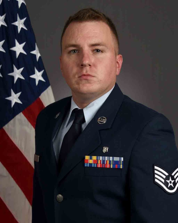 An airman in dress blues poses for a photo in front of a flag.