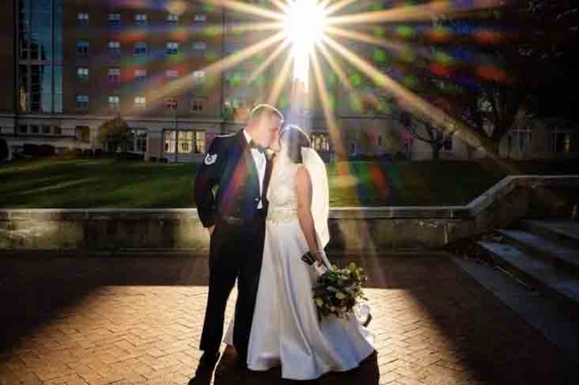 A couple in wedding attire kiss as the sun shines down on them.