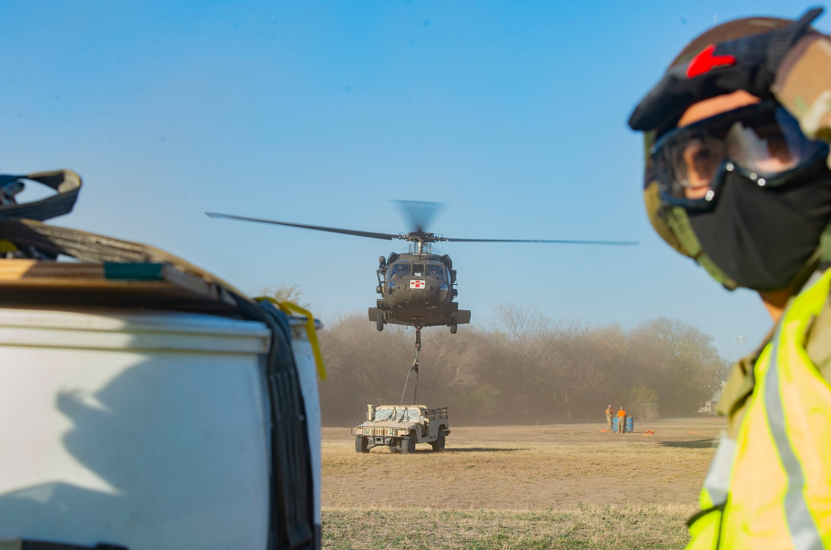 A U.S. Army UH-60L Black Hawk from Company C, 2nd Battalion, 149th Aviation Regiment prepares to pick up a Humvee sling load, Dec. 15, 2020, at Joint Base San Antonio-Chapman Annex, Texas.