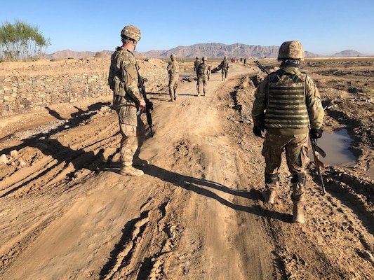 Sgt. Douglas King, of the Wisconsin Army National Guard's 829th Engineer Company assesses a road repair project in Afghanistan with a Romanian soldier in April 2020.