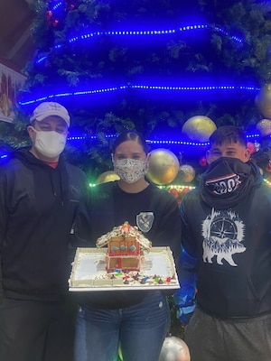 U.S. Army Spcs. Bailey Apodaca Weaver and Luke Welch and Cpl. James Bradley, air traffic controllers with Fox Company, 2-104th General Support Aviation Battalion, 28th Expeditionary Combat Aviation Brigade, show a gingerbread house they made for their commander's office.