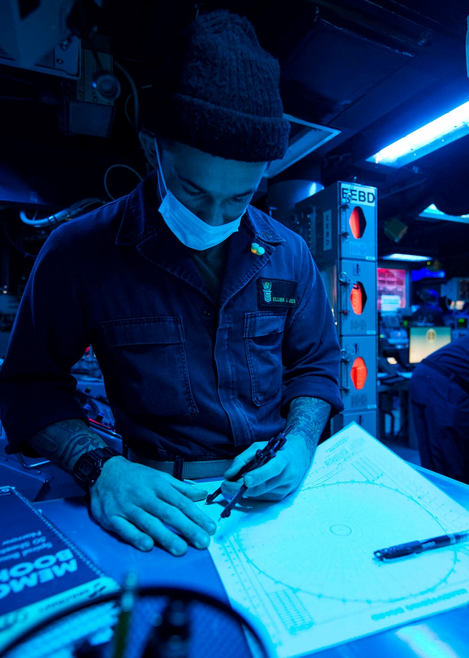 TAIWAN STRAIT (Dec. 30, 2020) Ensign Elijah Jones, from San Bernardino, California, plots on a maneuvering board in the combat information center as the guided-missile destroyer USS Curtis Wilbur (DDG 54) conducts routine operations. Curtis Wilbur is forward-deployed to the U.S. 7th Fleet area of operations in support of a free and open Indo-Pacific.