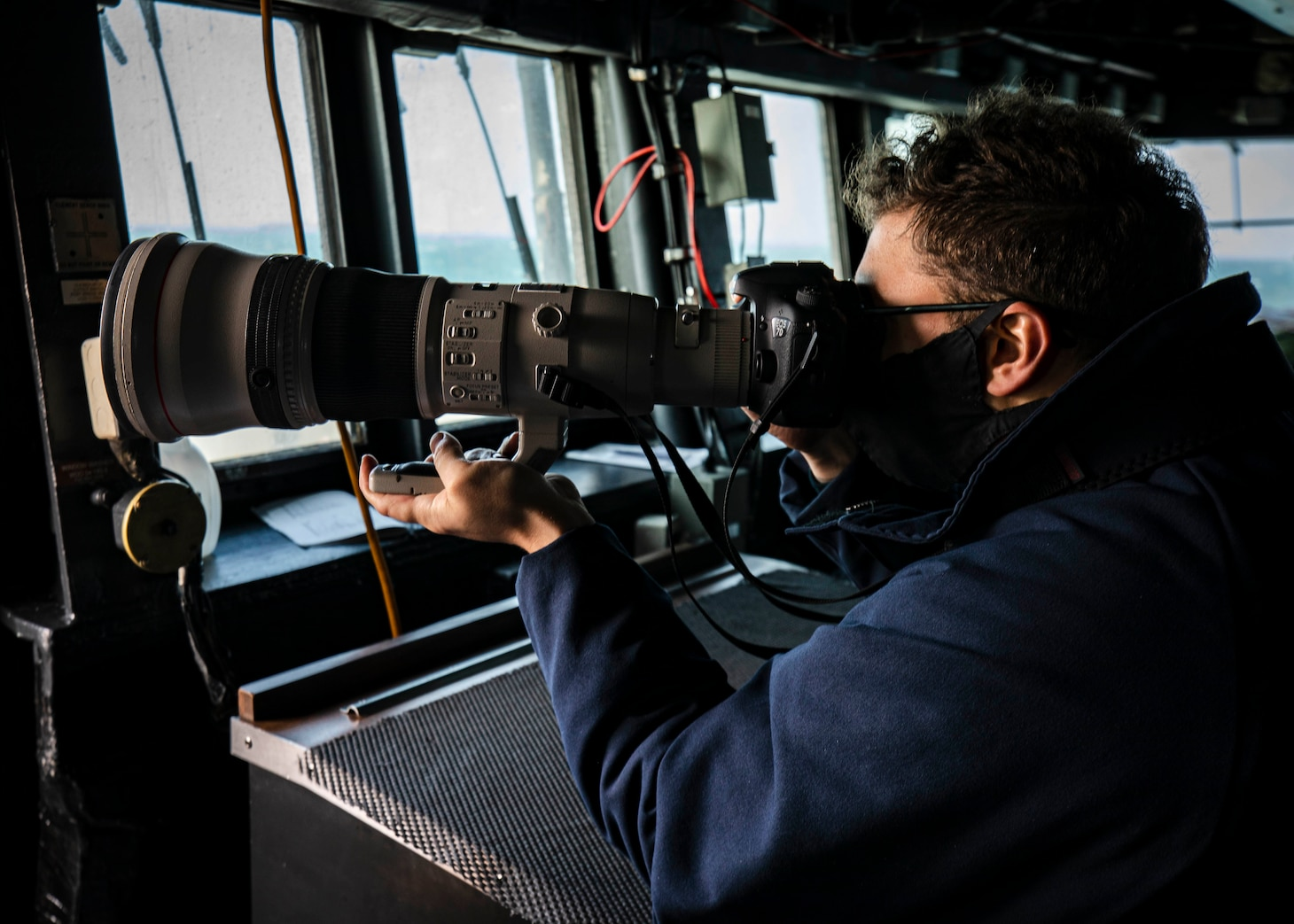 TAIWAN STRAIT (Dec. 30, 2020) Ensign Grayson Sigler, from Corpus Christi, Texas, scans the horizon while standing watch in the pilot house as guided-missile destroyer USS John S. McCain (DDG 56) conducts routine underway operations in support of stability and security for a free and open Indo-Pacific. Sea control is foundational for all other naval missions that support the Joint Force, including power projection.