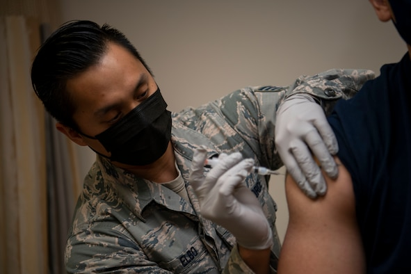 Staff Sgt. Michael Elbo, 509th Healthcare Operations Squadron NCO in charge of immunizations, administers a COVID-19 vaccine at Whiteman Air Force Base, Missouri, Dec. 30, 2020. The Whiteman AFB COVID-19 vaccine distribution and administration plan will implement a phased, standardized and coordinated strategy for prioritizing, distributing, and administering COVID-19 vaccines to installation personnel. (U.S. Air Force photo by Staff Sgt. Dylan Nuckolls)