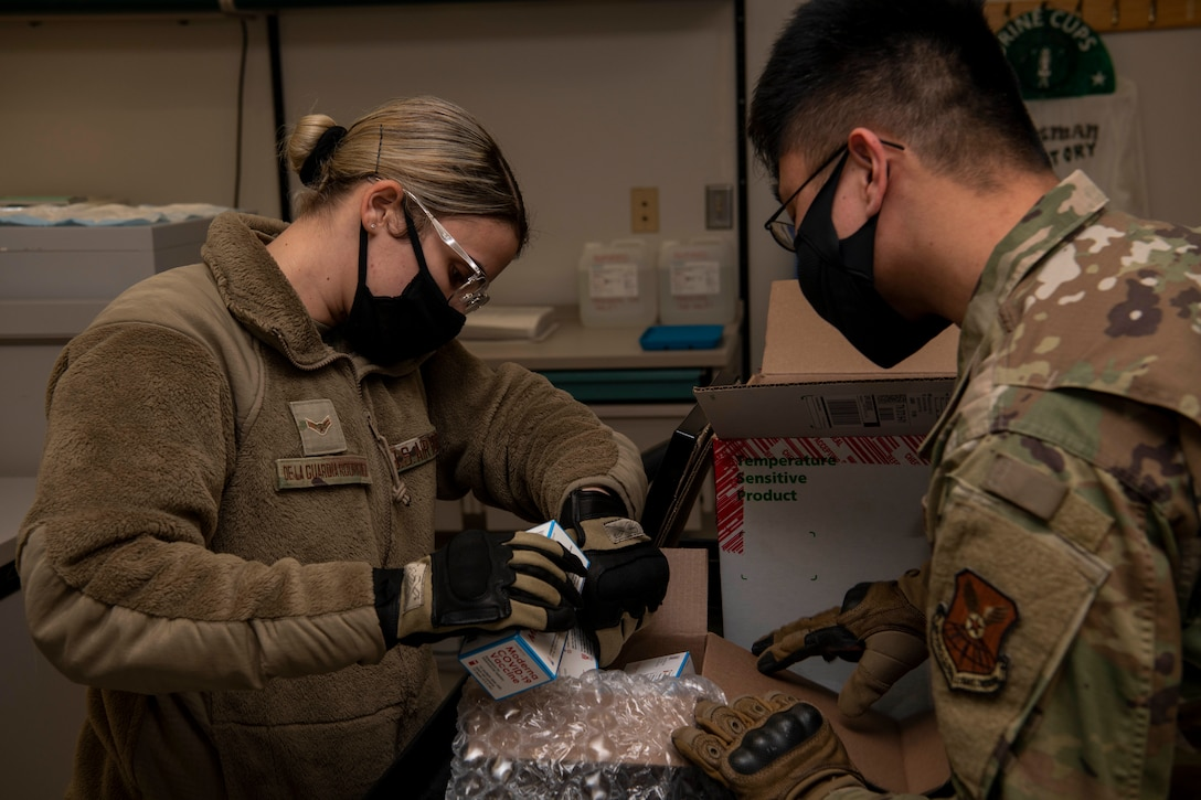 U.S. Air Force Airman 1st Class Jennifer De La Guardia Rodriguez, 509th Healthcare Operations Squadron medical logistics technician, left, and Staff Sgt. Allen Magbutay, 509th HCOS NCO in charge of medical materiel, examine the first shipment of the COVID-19 vaccine at Whiteman Air Force Base, Missouri, Dec. 30, 2020. The Whiteman AFB COVID-19 vaccine distribution and administration plan will implement a phased, standardized and coordinated strategy for prioritizing, distributing, and administering COVID-19 vaccines to installation personnel. (U.S. Air Force photo by Staff Sgt. Dylan Nuckolls)