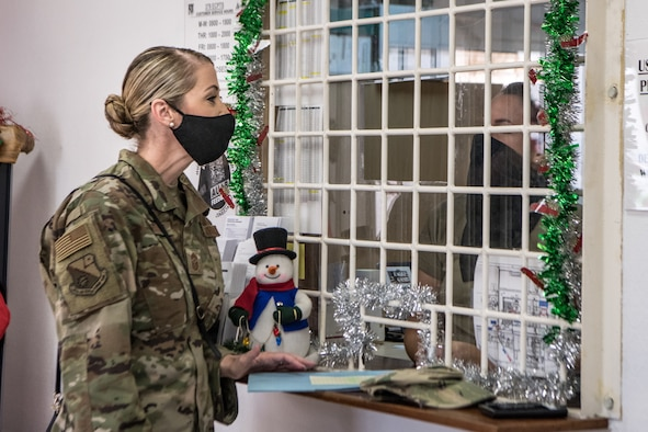 airman speaks at a service desk window to another person