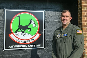 A man stands in uniform in front of a sign.