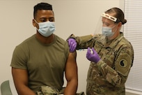 Capt. Wilifred Hale receives a COVID-19 vaccination from Sgt. Anna Carter Dec. 31, 2020, at Fort Pickett, Virginia.