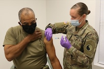 Command Sgt. Maj. Ronald Howell receives a COVID-19 vaccination from Sgt. Anna Carter Dec. 31, 2020, at Fort Pickett, Virginia.