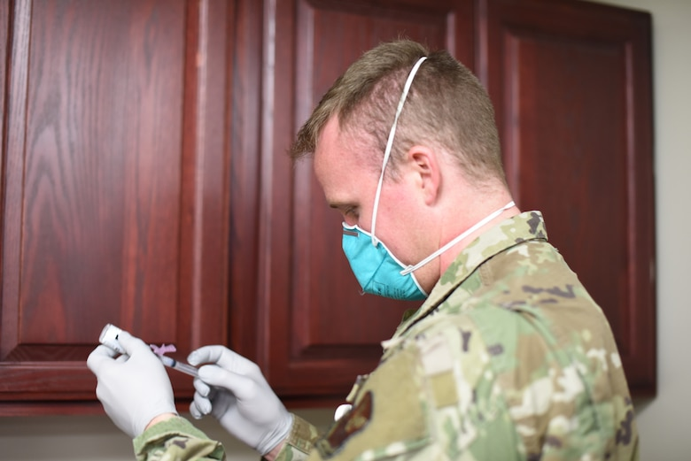 A member of the 341st Missile Wing Medical Group examines a dose of the COVID-19 vaccine.