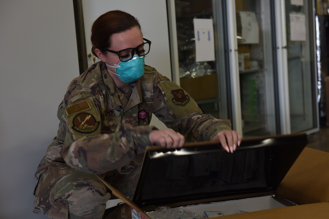 Senior Airmen Lauren Lacaprara, left, and Bayli Moore, 341st Healthcare Operations Squadron medical material technicians, open a shipment of delivered Maderna COVID-19 vaccines, Dec 30, 2020, at Malmstrom Air Force Base, Mont.