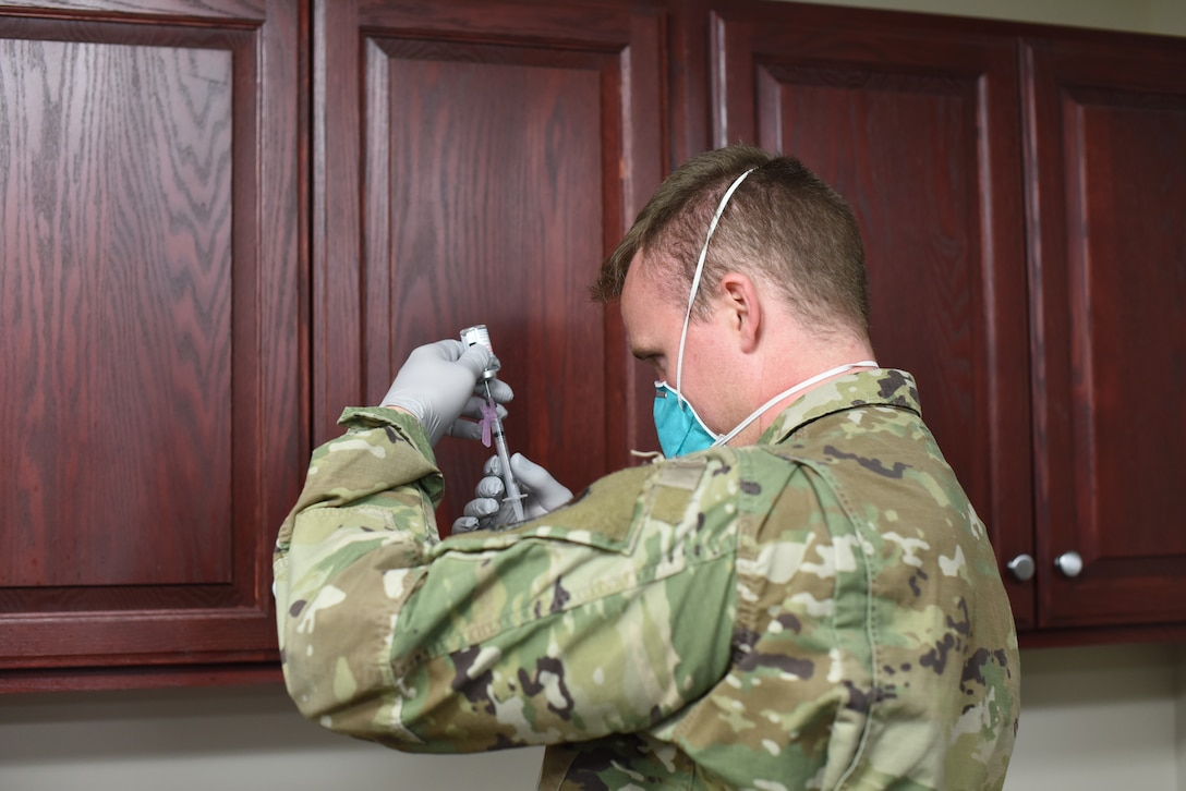 A member from the 341st Missile Wing Medical Group examines a dose of the COVID-19 vaccine, Dec. 31, 2020 at Malmstrom Air Force Base, Mont.