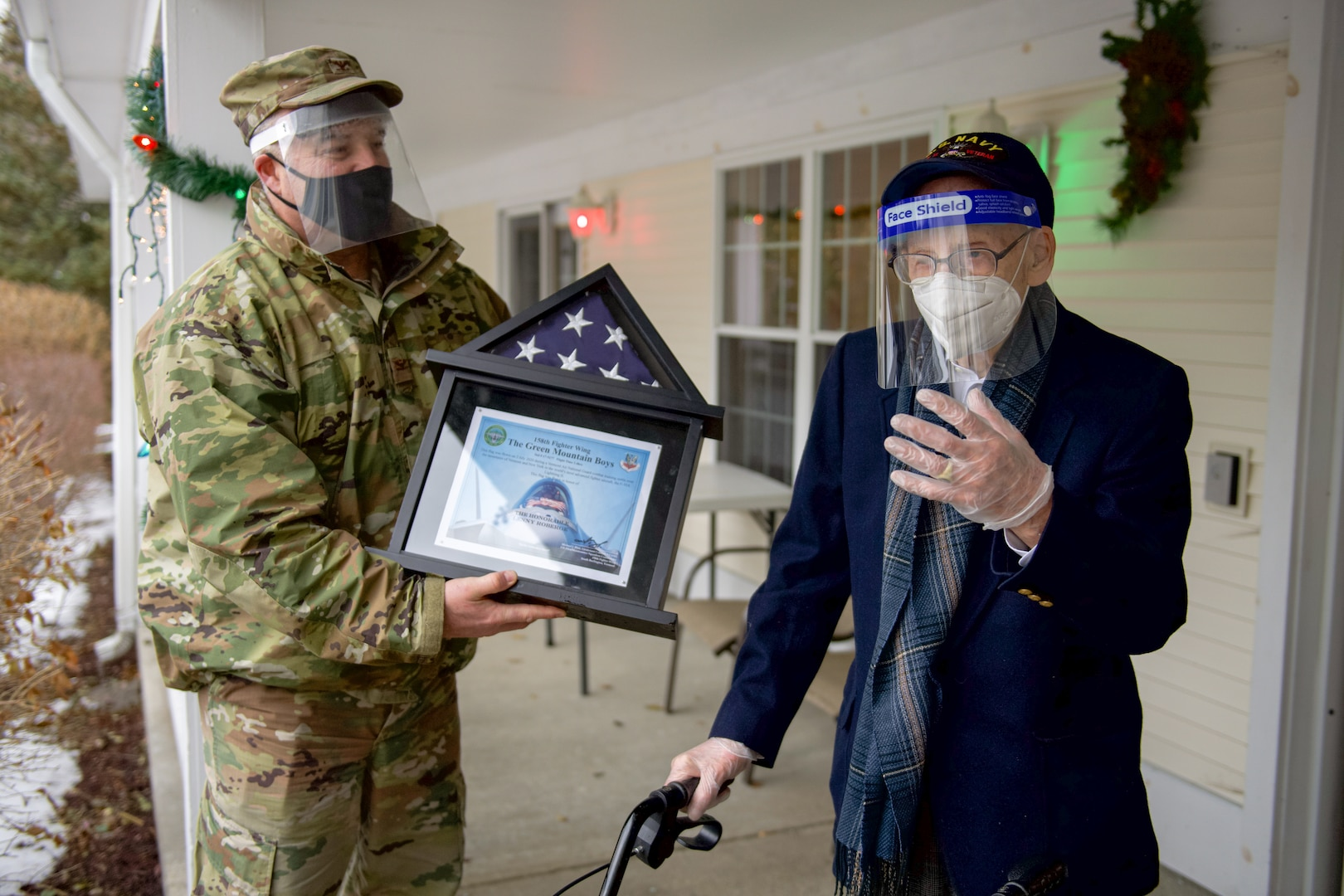 Col. Adam Rice, vice wing commander of the 158th Fighter Wing, Vermont Air National Guard, presents a flag flown in the F-35A Lightning II to WWII veteran Lenny Roberge, Vermont's oldest living veteran, outside his nursing home in South Burlington, Vt., Dec. 22, 2020. To honor Roberge, Airmen from the 158th Fighter Wing had a flag flown in an F-35 during a combat training sortie over the mountains of Vermont and New York.