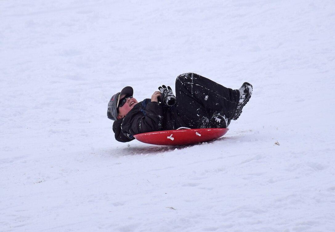 Boy sledding down a hill in a saucer