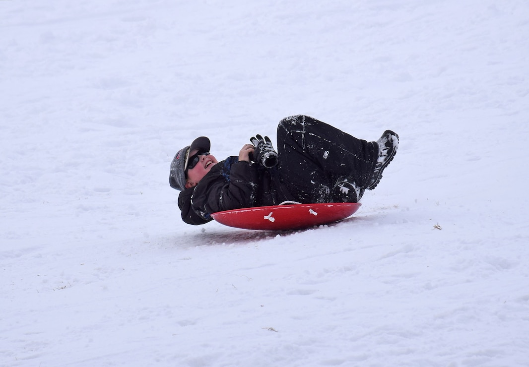 Boy sledding down a hill in a saucer