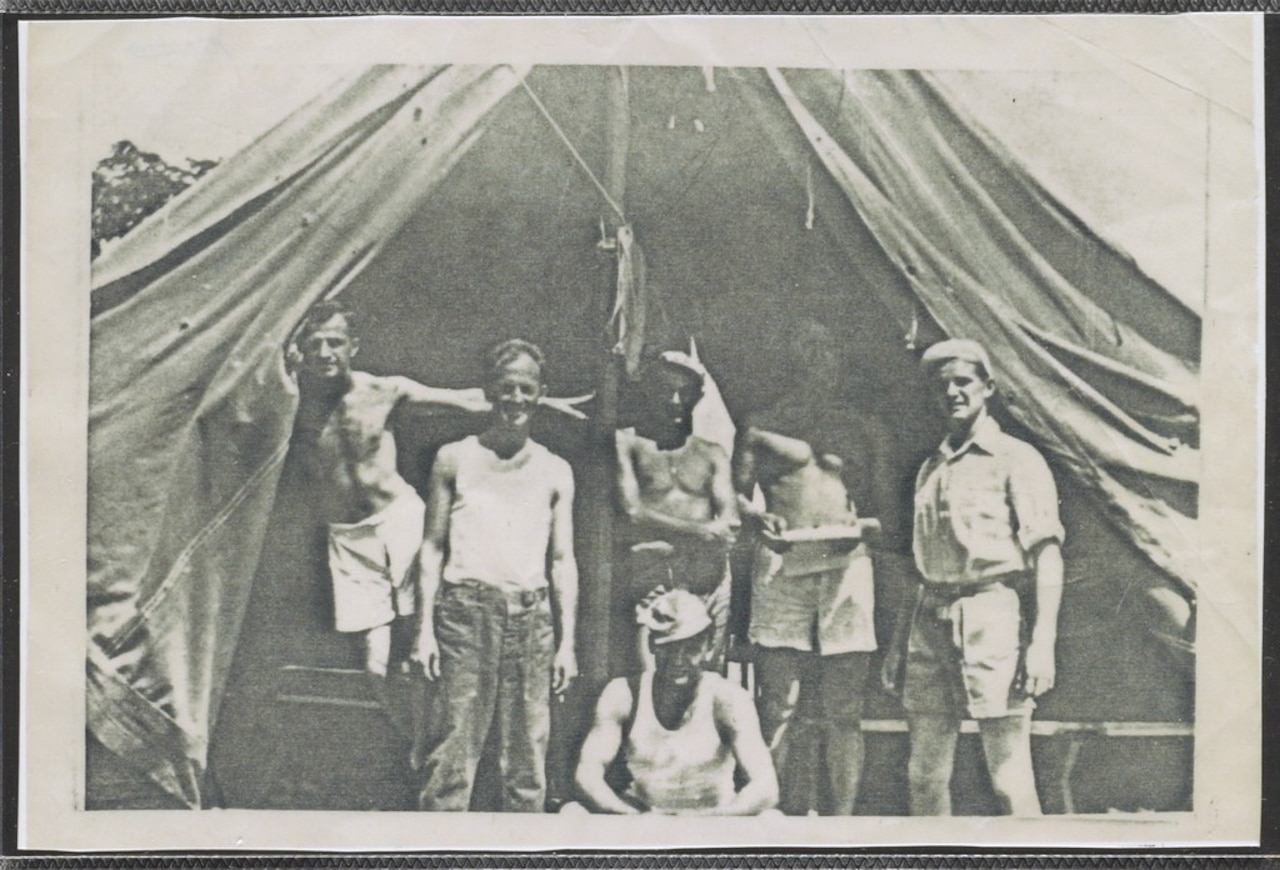 Six men stand inside a tent.