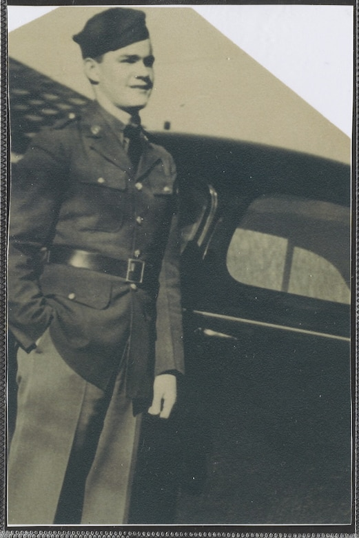 A man in a military uniform stands in front of a vehicle.