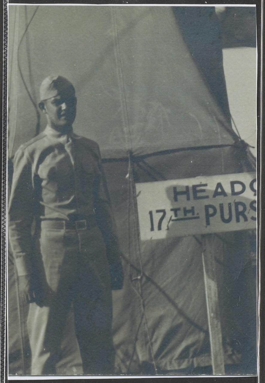 A man in a military uniform stands in front of a tent.